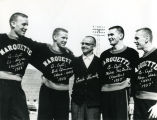 Captains Hoyle, Quinn, McGrath, and Voss standing with Coach Shimek, 1958?