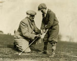 Frank J. Murray instructs his son with golf club, 1930? - 1935?