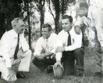 Frank J. Murray outside with football staff, 1947