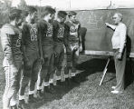 Frank J. Murray instructing football players at chalkboard, 1947? - 1949?