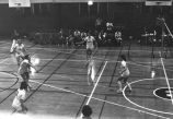 Maureen Feeney passes volleyball while team springs into action, 1976