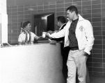 A student waits for a drink at the Schroeder Hall soda fountain, 1958