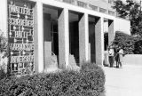 Two female students talk outside the main entrance to Schroeder Hall, 1976