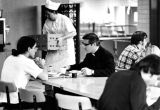 A priest and student dine at a table in the Schroeder Hall cafeteria, 1974