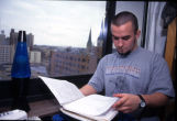 A student looks at his notes while studying in his Schroeder Hall dorm room, 1998