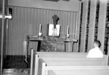 A student sits in a pew in the Schroeder Hall chapel, 1959