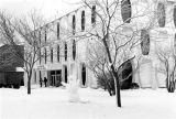 A snowman decorates the lawn in front of Lalumiere Hall