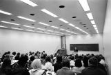 A professor lectures to a large class in Lalumiere Language Hall