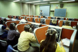A class sits at stations in one of the Lalumiere Hall language labs while an instructor leads from...