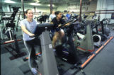 Women ride stationary bicycles in the exercise room at the Helfaer Recreation Center, 2002