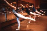 Dancers lift their legs into position at the barre