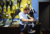 An employee of the Helfaer Recreation Center restrings a racquet, 1984