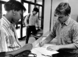 An employee completes paperwork with a patron at the service desk in the Helfaer Recreation...