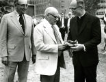 Evan P. Helfaer accepts a flag from Marquette University President Rev. John P. Raynor, S.J., 1973