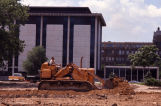A construction worker grades the ground east of the Wehr Chemistry Building
