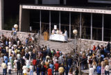 A number of priests participate in an event on the steps of the Wehr Chemistry Building