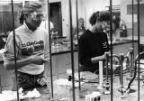 Two students work at stations in a chemistry laboratory class