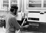 A student works with equipment in a chemistry laboratory, 1976