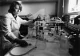 A chemistry professor sets up an experiment in a laboratory, circa 1983
