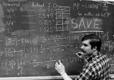 An unidentified male works at a blackboard to solve a physics equation
