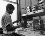 A physics student adjusts the controls on equipment in a laboratory, 1975