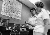 Sister Jeanette Mary Feldott discusses a physics experiment with a student, 1984