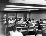 A professor lectures to students in the auditorium of the Wehr Life Sciences Building