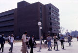 Students walk on the sidewalk outside the Business Administration Building, 1979