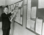 Herman Loebl checks job listings on a bulletin board in the Business Administration Building, 1967