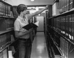 A student looks at journals in the Science Library stacks