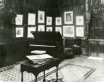 A variety of prints hang on the wall behind a piano in a music studio, circa 1925