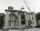 A bucket hangs from a crane over the John Plankinton Mansion, 1975