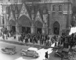 Parishioners in winter coats gather on the sidewalk outside Gesu Church, circa 1940