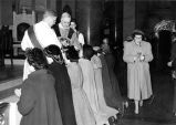 Priests distribute holy communion to young women at Gesu Church, circa 1945