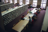 Students study at long tables amongst the current periodicals in Memorial Library, 1990