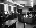 Staff members work at their desks in the Registrar's Office on the second floor of Johnston Hall,...