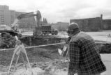 A surveyor takes measurements at the Alumni Memorial Union construction site, 1989