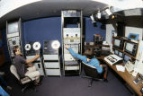Two staff members adjust the equipment in the control room of the Instructional Media Center (Room...