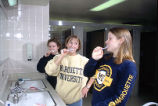 Three McCormick Hall residents brush their teeth in the women's restroom, 1998