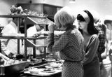 Two students select dishes from the line at the Cobeen Hall cafeteria, 1967-1968