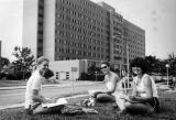 A trio of students study on the lawn across from Schroeder Hall