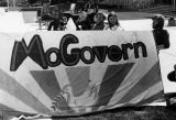 Students sit behind a George McGovern banner at an outdoor event, 1972-1973