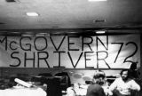 A large McGovern and Shriver banner hangs across a wall, 1972-1973