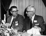 Robert Boden and Harold Hallows converse over dinner