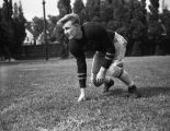 Dennis Wright crouches in a three-point stance, 1945-1948