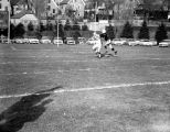 A Marquette football player covers a Holy Cross receiver, 1955
