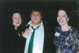 Chris Farley poses with two women