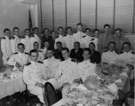 A class of new ensigns and second lieutenants pose in a semicircle at a dinner
