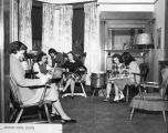 Women talk and read magazines in the Alumnae House reception room, circa 1940