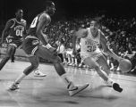 Kerry Trotter dribbles the basketball around an opponent from Stetson, 1985